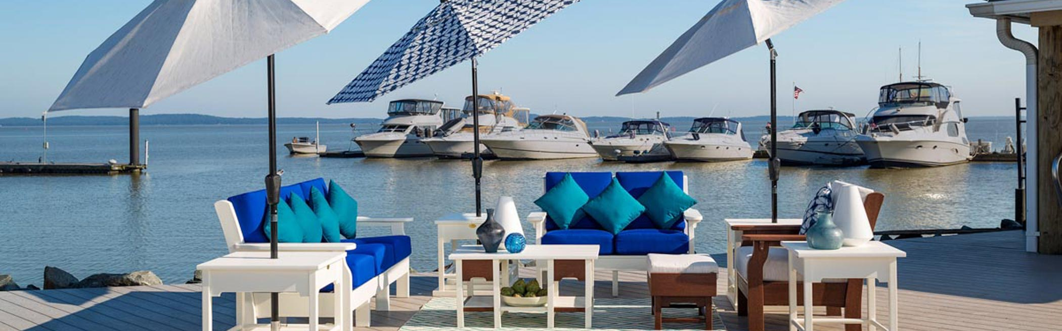 Van Buren Sofa, Love Seat, Chair, Coffee Table, End Table , Ottoman and Umbrella Stands on a dock with boats in the background