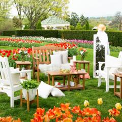 Two white Avonlea Garden Chairs, one Avonlea Garden Bench and 3 Avonlea Garden Side Tables sitting in a circle