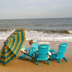 Turquoise poly adirondacks with beach umbrella on beach