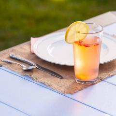 Cup of juice and place setting on poly table