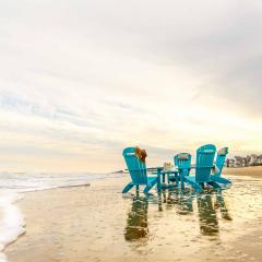 Four turquoise poly adirondack chairs on beach