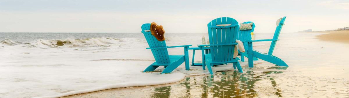 Four Aruba Blue Poly Adirondacks around Teal Blue Poly Coffee Table at the beach