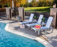 Three poly chaise lounges with adjustable backs and two poly side tables beside pool