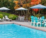 Poly poolside furniture including two chaise lounges with side tables, a bar with four bar stools and a bar height dining table with six bar height chairs
