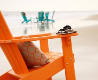 Orange poly adirondack chair with seat cushion at the beach