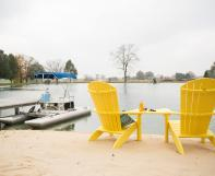 Two Yellow Poly Adirondack Chairs overlooking Lake