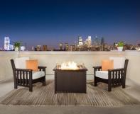 Keystone fire table and chairs on rooftop overlooking city in the evening.