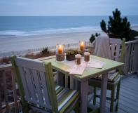 Square poly table with two chairs overlooking beach