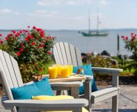 Two Great Bay Dining Chairs with a Great Bay Table Attachment on a dock by the ocean.