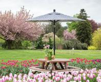 poly 48 inch round garden table with an umbrella and 40 inch curved garden benches in a tulip field