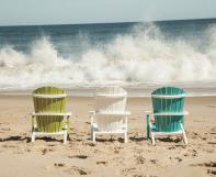 green, white and teal blue children's adirondacks on the beach