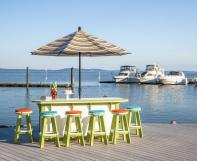 Striped outdoor umbrella with poly furniture bar and bar stools
